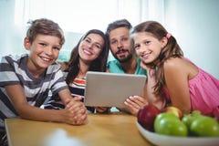 Porträt der lächelnden Familie unter Verwendung der digitalen Tablette beim bei Tisch sitzen stockbilder