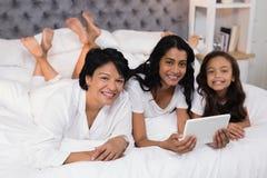 Porträt der lächelnden Familie von mehreren Generationen unter Verwendung der digitalen Tablette beim Lügen auf Bett stockbild