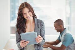 Porträt der lächelnden Frau, die digitale Tablette verwendet Lizenzfreie Stockfotografie