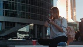 Porträt der lächelnden Frau, die Smartphonespracherkennung verwendet Junges kaukasisches Mädchen, das mit Kopfhörern und der Hers stock footage