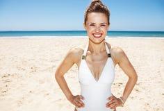 Porträt der lächelnden Frau im weißen Badeanzug am sandigen Strand Lizenzfreies Stockbild