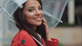 Porträt der lächelnden Frau unter Regenschirm in der Stadt, die die Kamera untersucht Frühlings- oder Herbsttag stock video