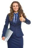 Porträt der lächelnden Geschäftsfrau mit dem Laptop, der sich Daumen zeigt Lizenzfreie Stockfotos