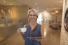Porträt der lächelnden Geschäftsfrau mit Kaffee Stockfotos