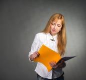 Porträt der lächelnden Geschäftsfrau mit Papierordner auf grauem Hintergrund. Stockbild