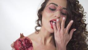 Porträt der lächelnden hübschen jungen gelockten saftigen Granatapfels der Mädchenholding Hälfte und Lecken ihrer Finger stock video