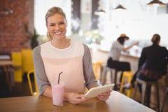 Porträt der lächelnden jungen blonden Frau, die mit Tablette und Milchshaken sitzt Lizenzfreie Stockfotos