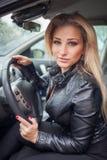 Porträt der lächelnden jungen blonden Frau im Auto Stockbilder