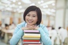 Porträt der lächelnden jungen Frau in der Bibliothek, die auf einem Stapel Büchern, Kamera betrachtend sich lehnt stockfotografie