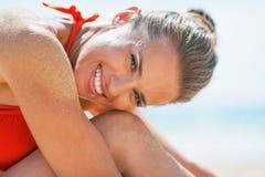 Porträt der lächelnden jungen Frau, die auf Strand sitzt Stockfotografie