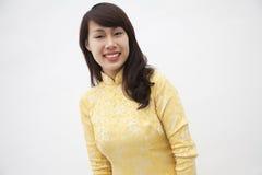 Porträt der lächelnden jungen Frau, die ein gelbes Trachtenkleid von Vietnam, Atelieraufnahme trägt Stockfotos