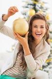 Porträt der lächelnden jungen Frau, die Weihnachtsball hält Lizenzfreie Stockfotografie