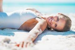 Porträt der lächelnden jungen Frau im Badeanzug ein Sonnenbad nehmend auf Strand Stockbild