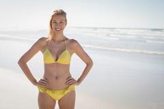 Porträt der lächelnden jungen Frau im gelben Bikini, der am Strand steht Stockbild