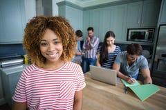Porträt der lächelnden jungen Frau mit Freunden im Hintergrund Stockfoto