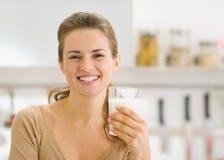 Porträt der lächelnden jungen Frau mit Glas Milch Stockbild