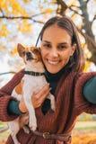 Porträt der lächelnden jungen Frau mit Hund draußen im Herbst Stockfotos