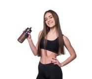 Porträt der lächelnden jungen sportlichen Frau mit einer Flasche Wasser aufwerfend im Studio lokalisiert auf weißem Hintergrund Stockfoto
