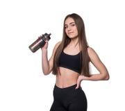Porträt der lächelnden jungen sportlichen Frau mit einer Flasche Wasser aufwerfend im Studio lokalisiert auf weißem Hintergrund Lizenzfreie Stockfotos