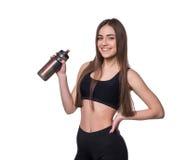 Porträt der lächelnden jungen sportlichen Frau mit einer Flasche Wasser aufwerfend im Studio lokalisiert auf weißem Hintergrund Stockfotografie