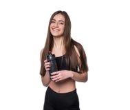 Porträt der lächelnden jungen sportlichen Frau mit einer Flasche Wasser aufwerfend im Studio lokalisiert auf weißem Hintergrund Lizenzfreie Stockfotografie