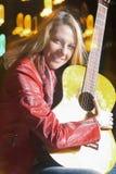 Porträt der lächelnden kaukasischen blonden Frau, welche draußen die Gitarre nachts spielt Stockbilder