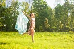 Porträt der lächelnden kaukasischen Frau, die barfüßigfreien mit fliegendem Halstuch laufen lässt stockfotos