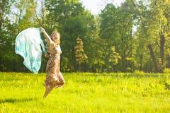 Porträt der lächelnden kaukasischen Frau, die barfüßigoudoors mit fliegendem Halstuch laufen lässt lizenzfreie stockfotografie