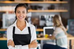Porträt der lächelnden Kellnerin stehend mit den Armen gekreuzt stockbild