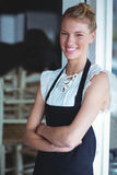 Porträt der lächelnden Kellnerin stehend mit den Armen gekreuzt lizenzfreie stockbilder
