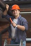Porträt der lächelnden männlichen Arbeitskraft, die Hausdachspitze repariert lizenzfreies stockbild