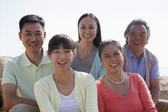 Porträt der lächelnden multigenerational Familie, die draußen auf den Felsen, China sitzt Lizenzfreie Stockfotografie