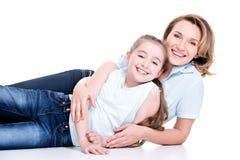 Porträt der lächelnden Mutter und der jungen Tochter lizenzfreie stockfotografie