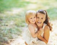 Porträt der lächelnden Mutter und des Babys draußen stockbilder