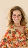Porträt der lächelnden reifen Frau mit roten runden Brillen Stockfotos