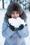Porträt der lächelnden reifen Frau mit Schnee in den Händen Lizenzfreie Stockbilder