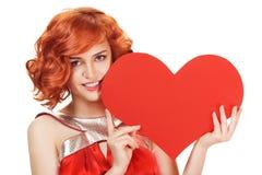 Porträt der lächelnden roten Haarfrau, die großes rotes Herz hält Stockbilder