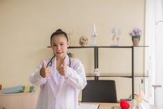 Porträt der lächelnden schönen asiatischen Ärztin, die zwei Bums herauf Zeichen an der Krankenhaus-, glücklicher und positiverhal stockbilder