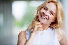 Porträt der lächelnden schönen jungen Frau, die ihr Haar berührt Stockbilder
