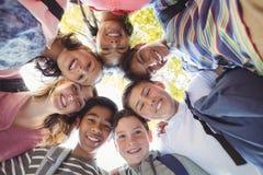 Porträt der lächelnden Schule scherzt die Formung eines Wirrwarrs im Campus lizenzfreie stockfotografie