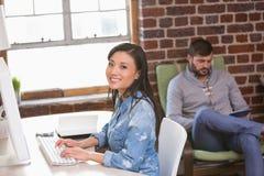 Porträt der lächelnden weiblichen Exekutive, die Computer verwendet Lizenzfreie Stockfotos