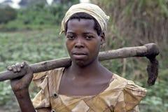 Porträt der ländlichen Frau mit Hacke auf Schulter Stockbild
