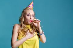 Porträt der lustigen blonden Frau im Geburtstagshut und im gelben Hemd auf blauem Hintergrund Feier und Partei Stockfoto