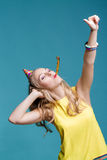 Porträt der lustigen blonden Frau im Geburtstagshut und im gelben Hemd auf blauem Hintergrund Feier und Partei Stockbilder