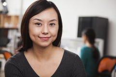 Porträt der mittleren erwachsenen Geschäftsfrau im Büro Stockfotografie