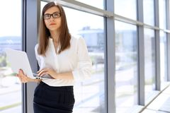 Porträt der modernen Geschäftsfrau, die mit Laptop-Computer im Büro, Kopienraumbereich arbeitet Lizenzfreie Stockfotos