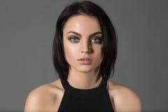 Porträt der modernen netten Frau des kurzen Haares, die Kamera auf Grau betrachtet Stockfotos