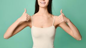Porträt der modischen jungen Frau, die Daumen oben über grauem Hintergrund zeigt stockbilder