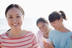 Porträt der multi- Generations-Afamilie auf dem Strand, Shell betrachtend lizenzfreies stockfoto