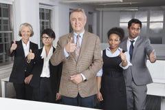 Porträt der multiethnischen Geschäftsgruppe Daumen im Büro oben gestikulierend stockfotos